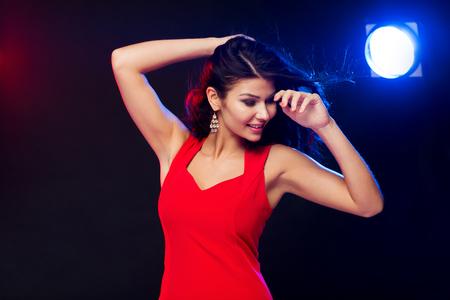 bailes latinos: la gente, días de fiesta, disco, estilo de vida nocturna y de ocio concepto - mujer atractiva en el baile vestido rojo en el club nocturno Foto de archivo