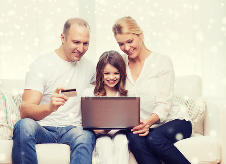 finance girl: family, shopping, technology and people concept - happy family with laptop computer and credit card over snowflakes background
