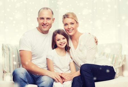 schöne frauen: Familie, Kindheit, Menschen und nach Hause Konzept - lächelnd Eltern mit kleinen Mädchen sitzen und zu Hause umarmen