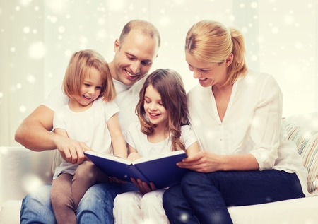 girl bonding: family, leisure, education and people - smiling mother, father and little girls reading book over snowflakes background