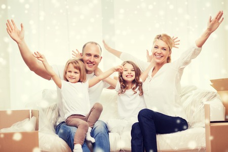 smiling parents and two little girls moving into new home and waving hands over snowflakes background