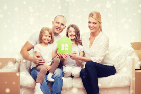 house family: smiling parents and two little girls moving into new home and waving hands over snowflakes background