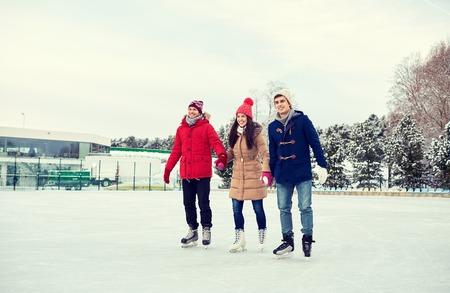 amicizia: felice pattinaggio amici ghiaccio sulla pista di pattinaggio all'aperto Archivio Fotografico
