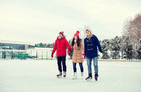 patinaje sobre hielo: feliz de patinaje sobre hielo en la pista de amigos al aire libre