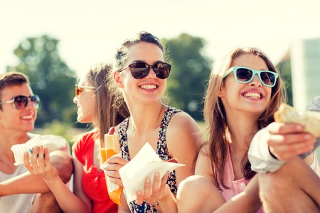 group of smiling friends in sunglasses sitting with food on city square Stock Photo