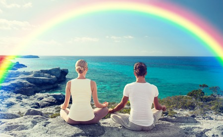 team lotus: happy couple meditating in lotus pose on summer beach from back