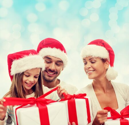 santa helper: happy family in santa helper hats with gift boxes sitting over blue lights background Stock Photo