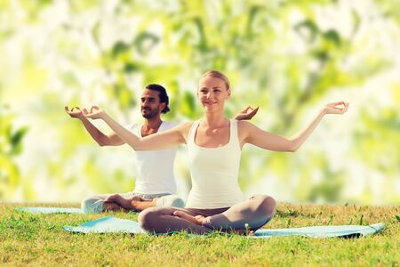 couple nature: smiling couple meditating and sitting on mats over green tree leaves background