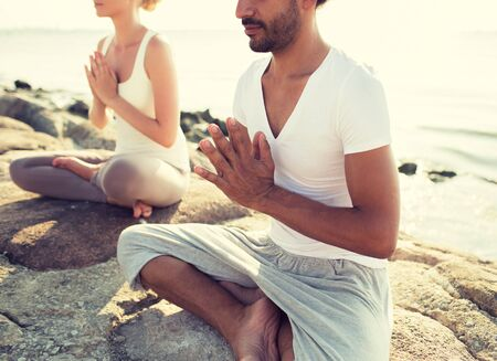 team lotus: close up of couple making yoga exercises sitting on pier outdoors