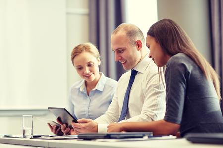 trabajo en equipo: sonriendo equipo de negocios con ordenador que cumpla Tablet PC en la oficina Foto de archivo