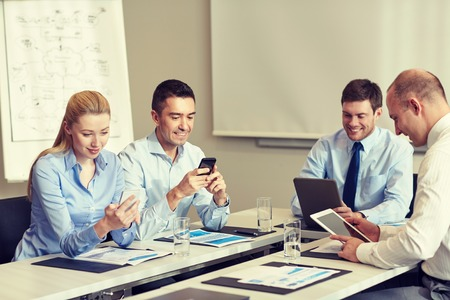 business partners: smiling business team with smartphone and papers meeting in office