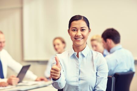 business planning: smiling businesswoman showing thumbs up with group of business people meeting in office
