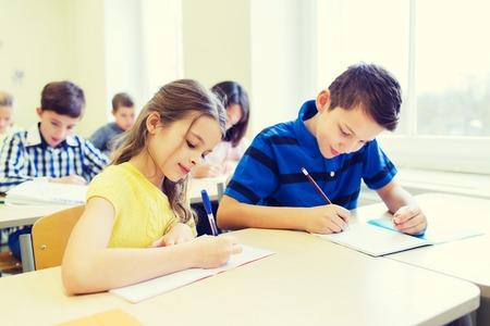 convivencia escolar: grupo de niños de la escuela con lápices y cuadernos escribía la prueba en el aula
