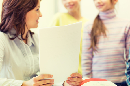 teacher: close up of school kids and teacher with papers talking in classroom Stock Photo