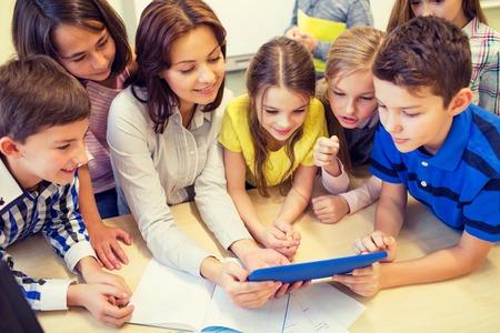 maestra enseñando: grupo de niños de la escuela con el maestro mira al ordenador Tablet PC en el aula Foto de archivo
