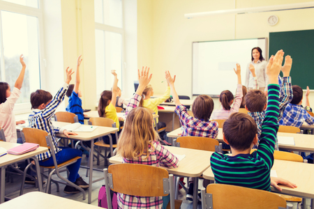 preteen boy: group of school kids with teacher sitting in classroom and raising hands Stock Photo