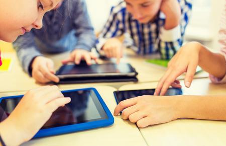niños jugando en la escuela: close up de niños de escuela con computadoras tablet pc divirtiéndose y jugando en las vacaciones en el aula