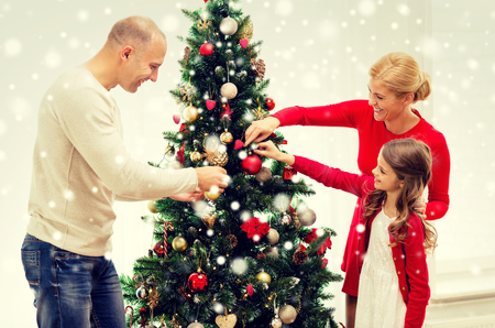 home decorating: smiling family decorating christmas tree at home