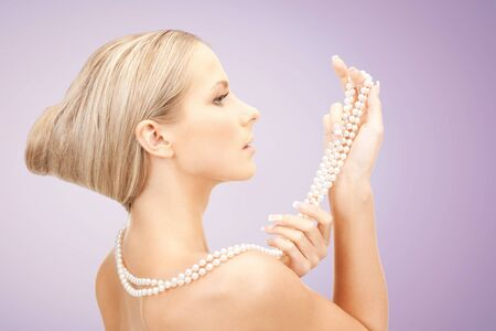 pearl necklace: beautiful woman with sea pearl necklace or beads in hand over violet background