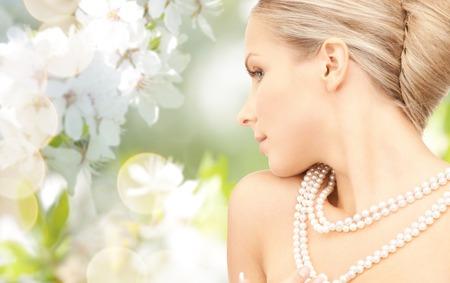 mooie vrouw met zee parelsnoer of kralen over kersenbloesem achtergrond Stockfoto