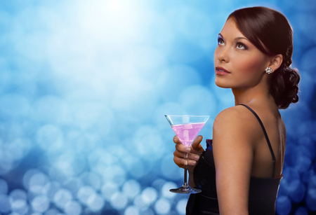 celebrities: smiling woman in evening dress holding cocktail over blue lights background