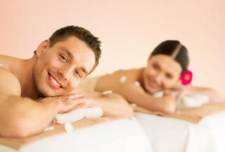 massage homme: image d'un couple dans le salon spa couché sur les bureaux de massage
