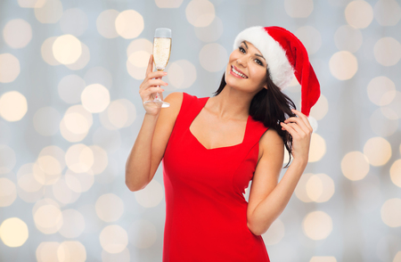 sexy dress: beautiful sexy woman in santa hat and red dress with champagne glass over lights background