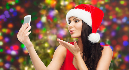 hot chick: beautiful sexy woman in red santa hat taking selfie picture by smartphone and sending blow kiss to camera