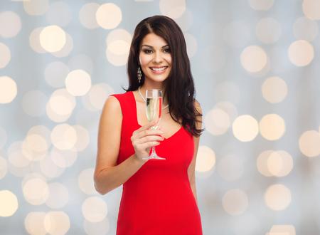 조명 배경 위에 샴페인 유리와 빨간 드레스에서 아름 다운 섹시 한 여자