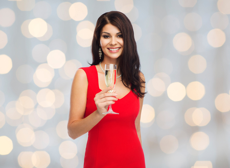 donne eleganti: bella donna sexy in abito rosso con bicchiere di champagne su sfondo di luci