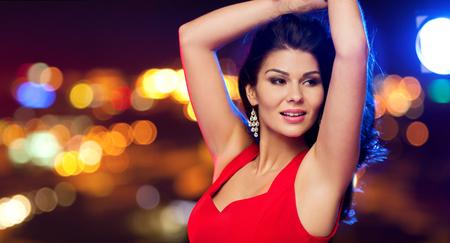 baile latino: hermosa mujer sexy en el baile vestido rojo durante la noche luces de la calle de fondo