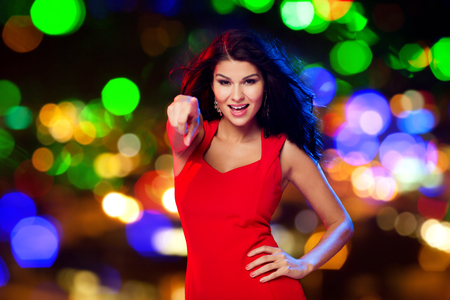 street party: beautiful sexy woman in red dress pointing finger on you at disco over night street lights background