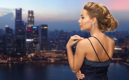 jewel: beautiful woman with diamond earring over night singapore city background