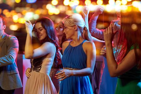 despedida de soltera: grupo de amigos felices bailando en la discoteca