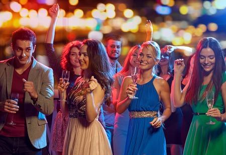happy friends with glasses of non-alcoholic champagne dancing at disco in nightclub Foto de archivo