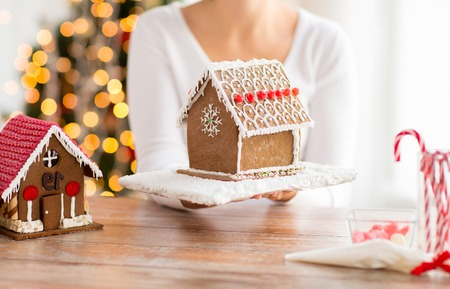sugarcoated: close up of happy woman holding and showing gingerbread house at home Stock Photo