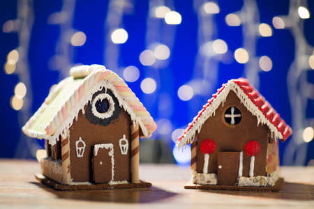 casita de dulces: closeup of beautiful gingerbread houses on table over blue garland lights Foto de archivo