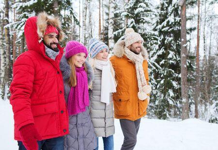 grupo de hombres: grupo de sonrientes hombres y mujeres caminando en el bosque de invierno