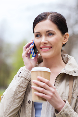 mobile phones: smiling woman with coffee calling and talking on smartphone in park