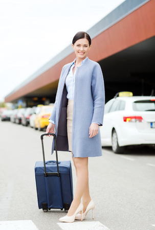 railway transportation: smiling young woman with travel bag over taxi at airport terminal or railway station Stock Photo