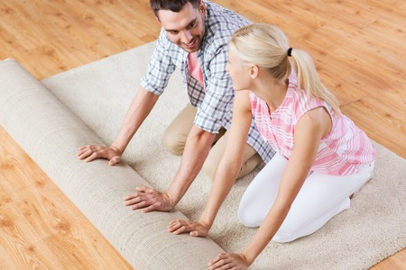 carpet and flooring: happy couple unrolling carpet or rug on floor at home Stock Photo