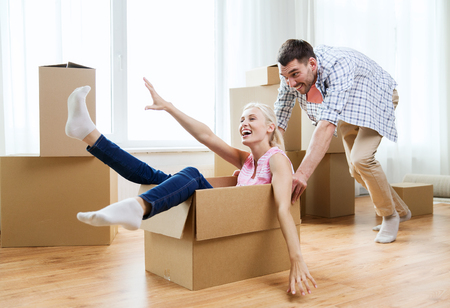 people moving: happy couple having fun and riding in cardboard boxes at new home Stock Photo
