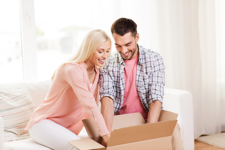happy couple opening cardboard box or parcel at home