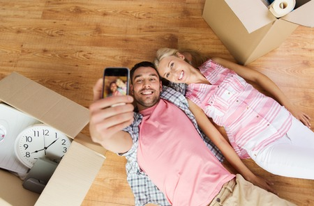 family moving house: happy couple taking selfie with smartphone and lying on floor among cardboard boxes at home