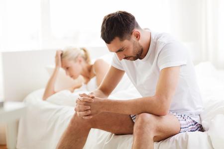 enamorados en la cama: pareja infeliz que tiene problemas en el dormitorio Foto de archivo