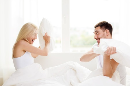 romance bed: happy couple having pillow fight in bed at home Stock Photo
