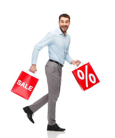 excited man: smiling man walking with red shopping bags Stock Photo