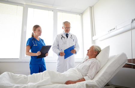 doctor and nurse with clipboards visiting senior patient woman at hospital ward Stock Photo