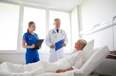hospitales: m�dico y enfermera con portapapeles visitan mujer mayor paciente en sala de hospital