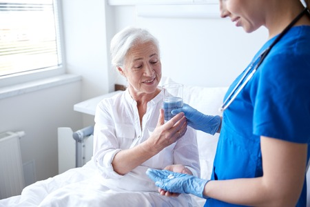 health care: nurse giving medication and glass of water to senior woman at hospital ward Stock Photo